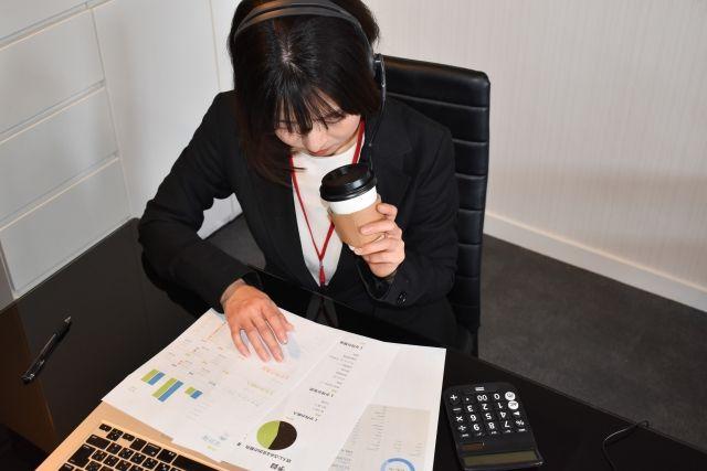 コーヒーを飲みながら資料をチェックする女性